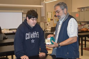 Robotics student getting help from Mr. Badaoui.