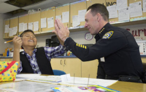 Sunnyvale Police Chief Frank Grgurina high fives his reading partner, Kevin Cuevas.