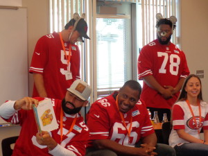 49er Michael Wilhoite reads If You Take a Mouse to School aloud while 49ers Bradley Pinion and Garrison Smith act it out