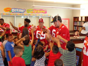 49ers high five Lakewood Elementary students after reading to them in the library.