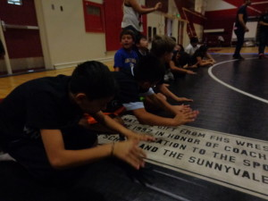Students pound the mat as they cheer each other on at final wrestling tournament.