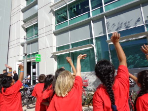Third graders wave at Google employees sending them friendly messages via Post-its on their 2nd floor windows.