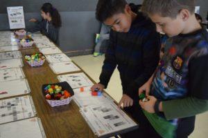 Middle school boys figure out math problem using cubes