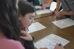 Middle school girls work on math problems together