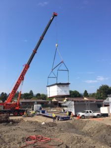 crane lowers prefabricated classroom onto ground at Bishop