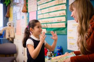 little girl tells her teacher a story with her hands