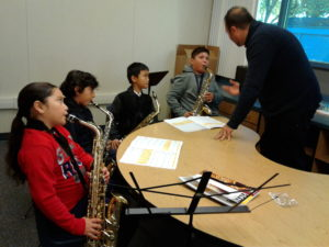 students practice their saxophones in their classroom
