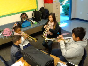 students practice their trumpets in a classroom