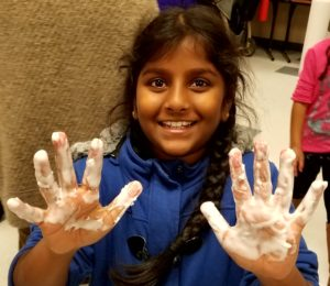 smiling student with sticky hands from science experiment