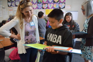 student shares his leadership notebook with visitor