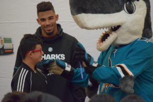 San Jose Sharks Evander Kane and SJ Sharkie hand out glasses to students