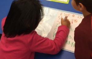 kindergarteners working together at their desk