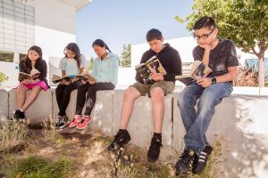 students reading in a group outside