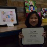 third grader with her winning artwork at county office of education